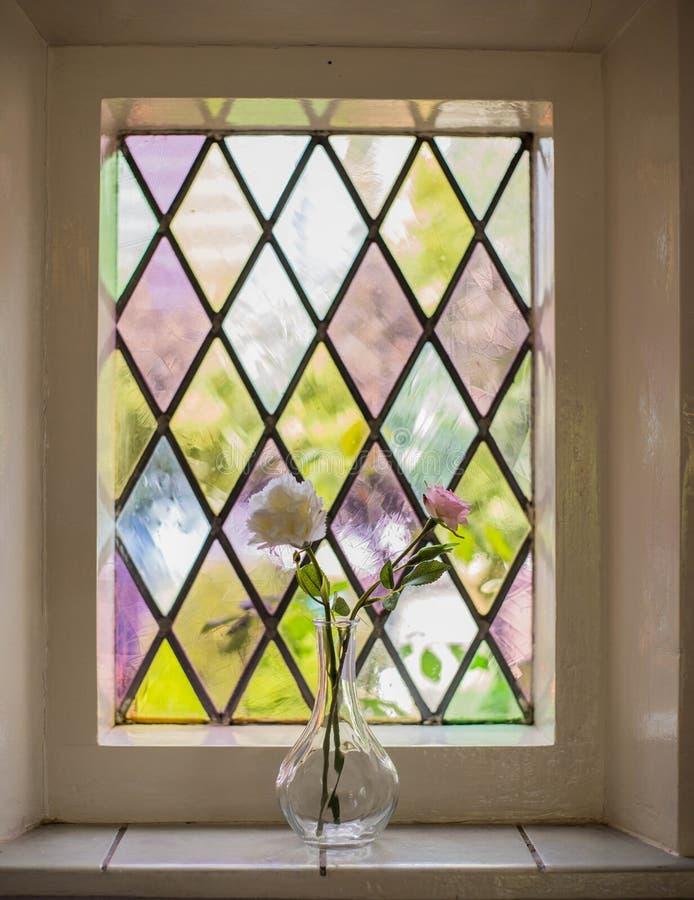与花的五颜六色的彩色玻璃在光的花瓶 免版税库存图片