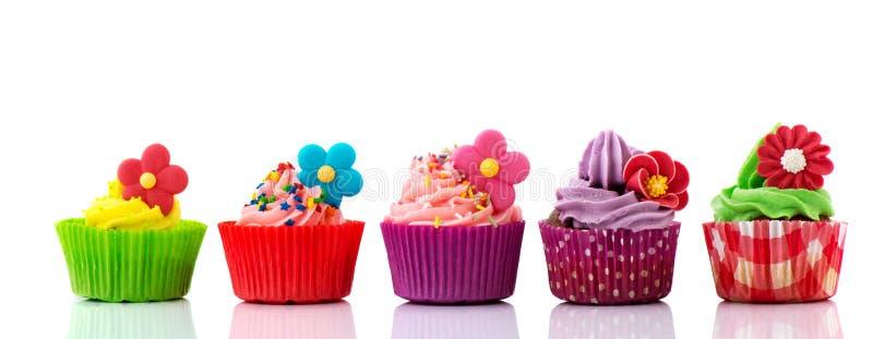 与花的五颜六色的杯形蛋糕 库存照片