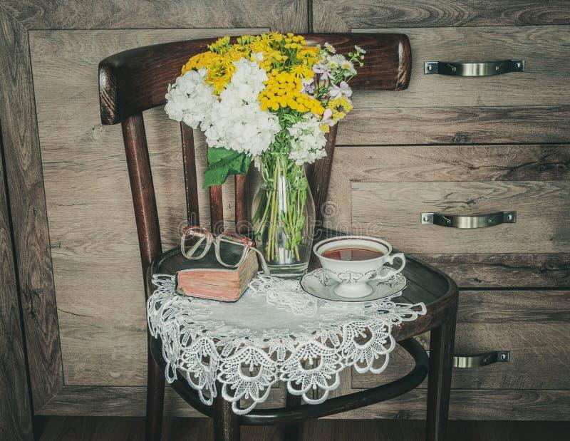 与花的减速火箭的椅子在花瓶、一本老祈祷书和一杯茶 库存照片
