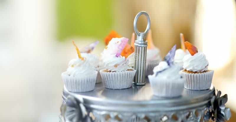 与花的可口五颜六色的婚姻的杯形蛋糕和蝴蝶和美丽的给上釉的蛋糕 免版税库存照片