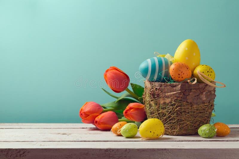 与花的复活节彩蛋装饰在蓝色背景 免版税库存图片