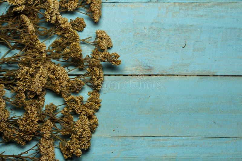 与花的干草在一张木桌上 免版税库存图片