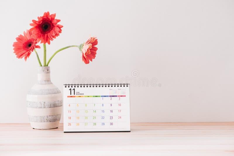 与花的日历在白色桌上的花瓶 免版税库存照片