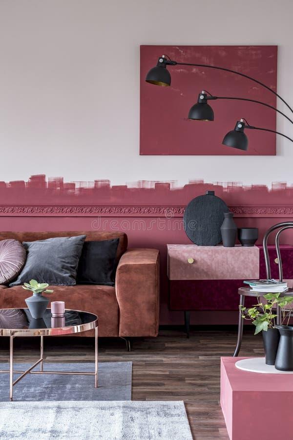 与花的时髦的圆的咖啡桌在小罐和茶杯在时兴的客厅内部 库存照片