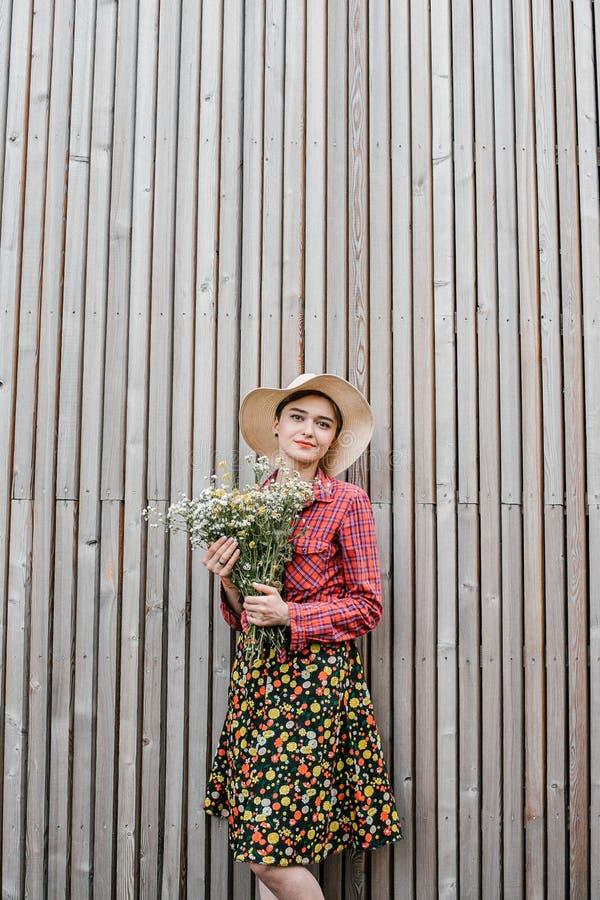 与花的时髦的女孩身分 在木墙壁附近的美女 春天样式 夏天步行 r ?treadled 免版税图库摄影