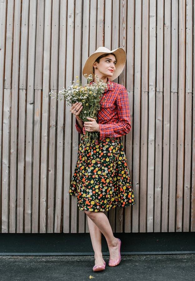 与花的时髦的女孩身分 在木墙壁附近的美女 春天样式 夏天步行 r ?treadled 免版税库存图片