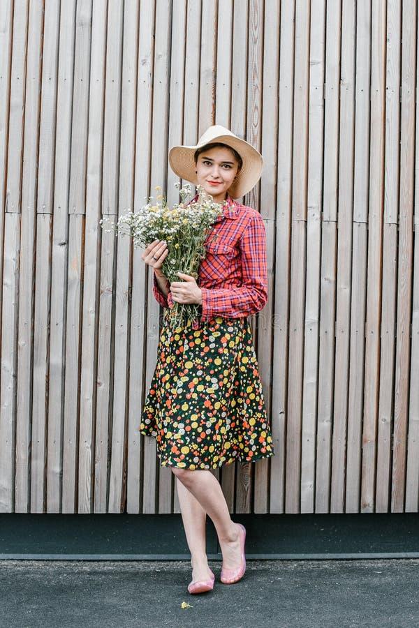 与花的时髦的女孩身分 在木墙壁附近的美女 春天样式 夏天步行 r ?treadled 库存图片
