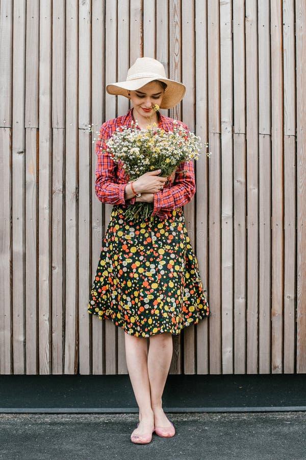 与花的时髦的女孩身分 在木墙壁附近的美女 春天样式 夏天步行 r ?treadled 图库摄影