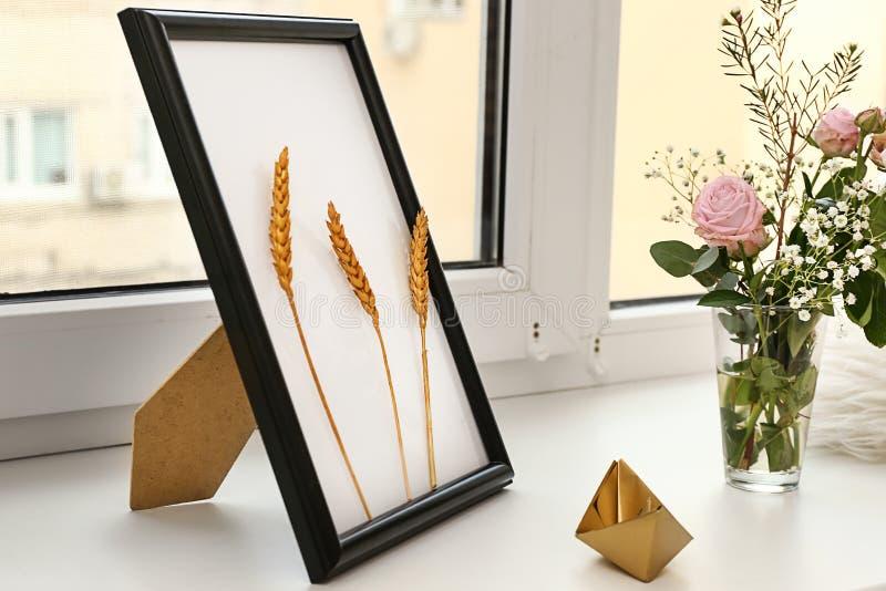与花的时髦的金黄装饰在窗台的花瓶 库存图片