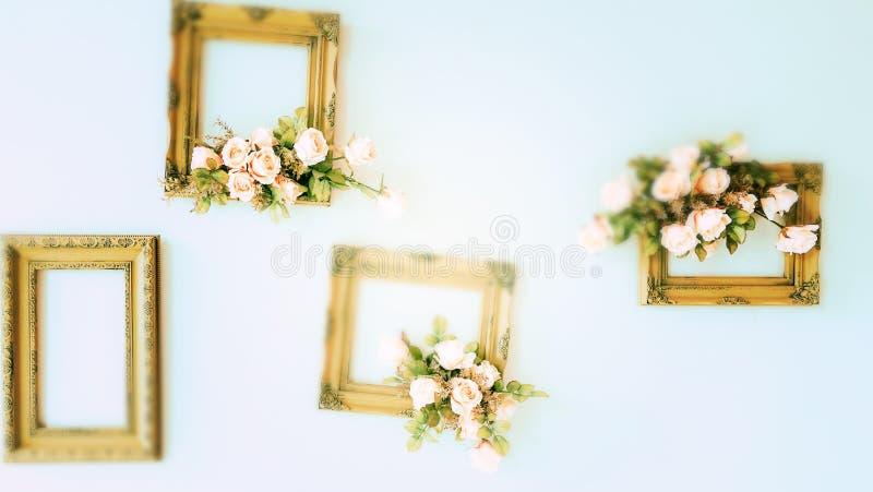 与花的模糊的金黄木制框架在墙壁上 库存图片