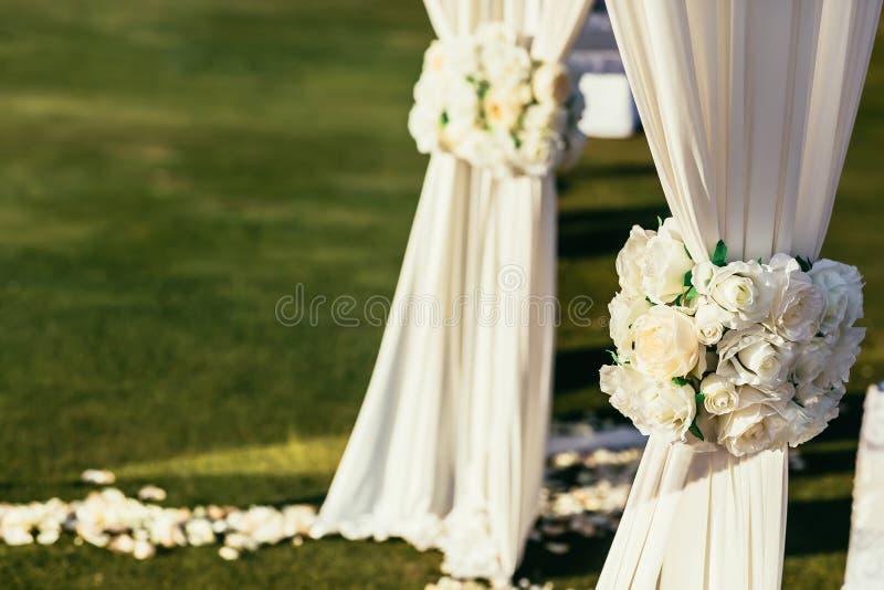 与花的白色婚礼曲拱在晴天在仪式放 免版税库存图片
