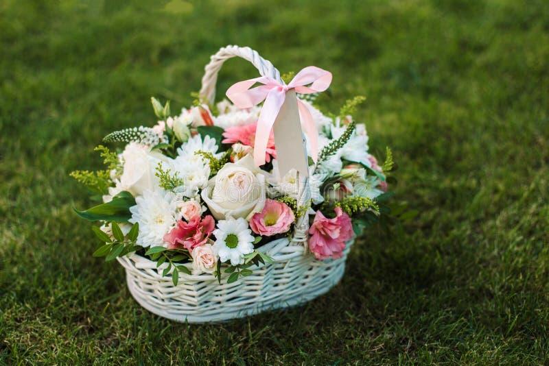 与花的礼物篮子在绿色草坪 免版税库存照片