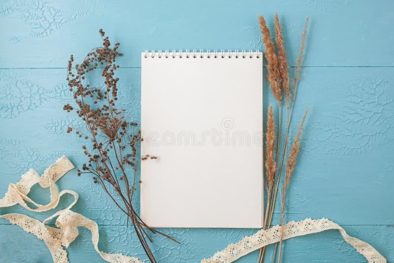 与花的空白的明信片在创造性的工作设计的蓝色木背景 文本的空间 免版税库存图片