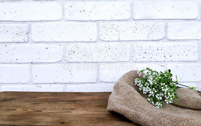与花的空的木桌和在白色砖墙背景的粗麻布织品 免版税库存照片