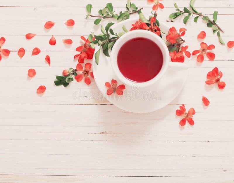 与花的红色茶在木背景 免版税库存图片