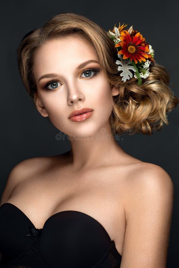 与花的美丽的妇女画象在头发 免版税库存照片