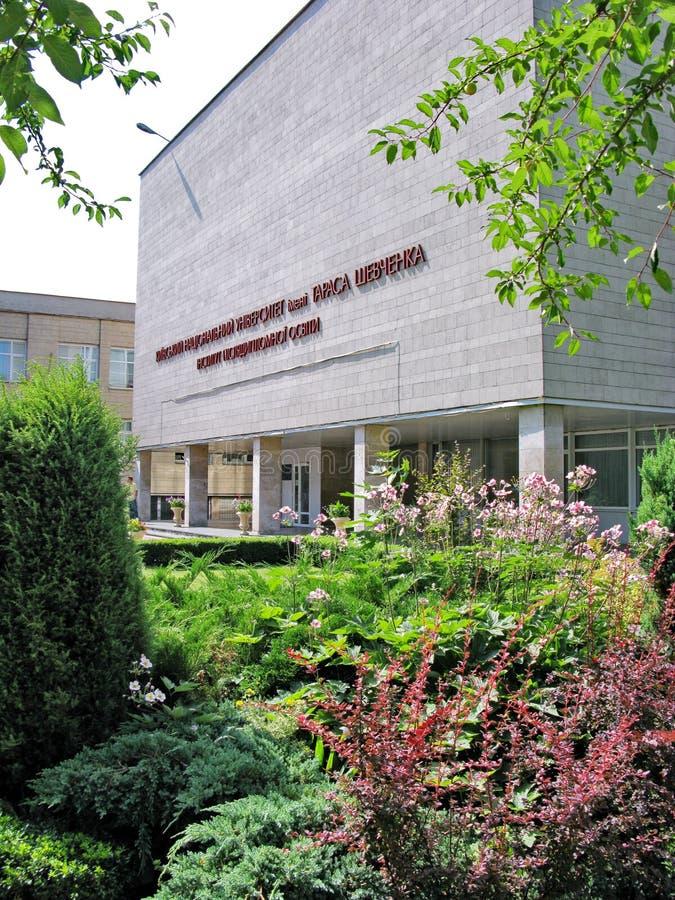 与花的美丽的花床和在教育机构附近的绿色草坪灰色砖大厦的  免版税库存照片
