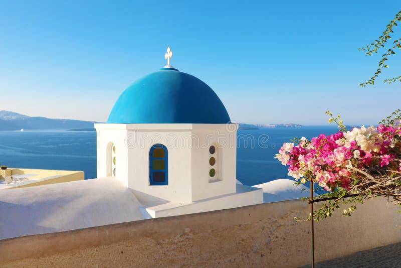 与花的蓝色教会圆顶在Oia,圣托里尼典型的希腊村庄  库存图片