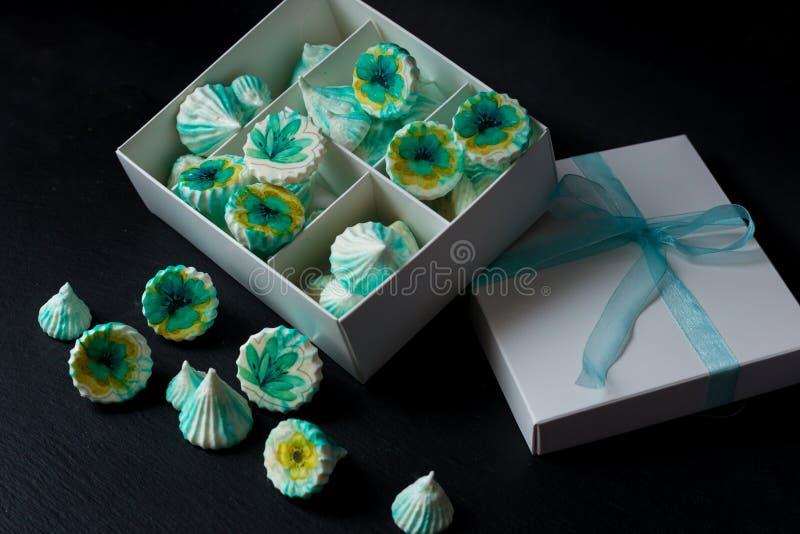 与花的蛋白甜饼绿色在白色箱子 库存照片