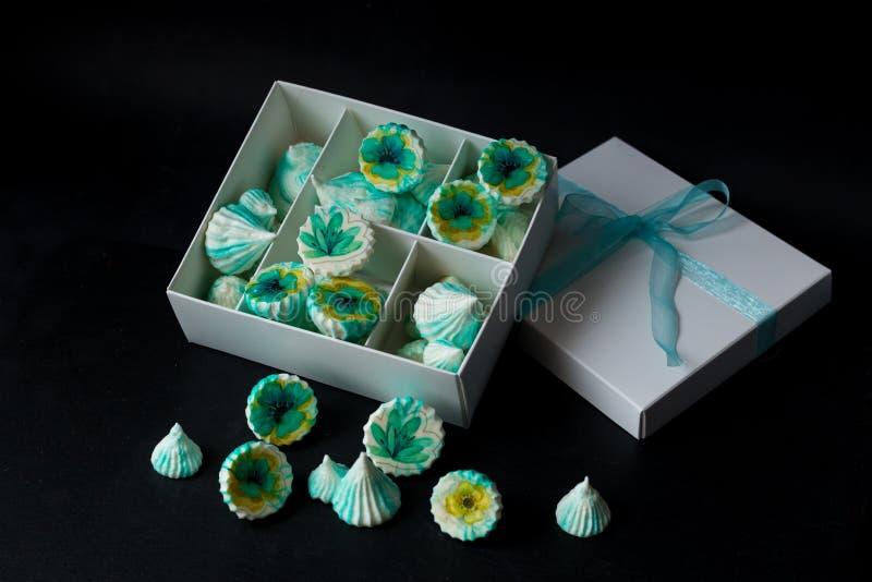 与花的蛋白甜饼绿色在白色箱子 免版税图库摄影