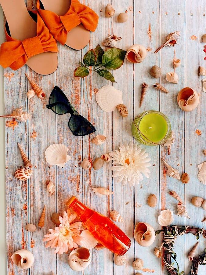 与花的贝壳和海石头在木背景夏天休假概念摘要妇女辅助部件sunglass帽子凉鞋 库存图片