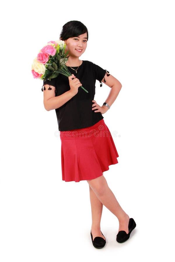 与花的逗人喜爱的女孩姿势,全长结束白色 免版税图库摄影