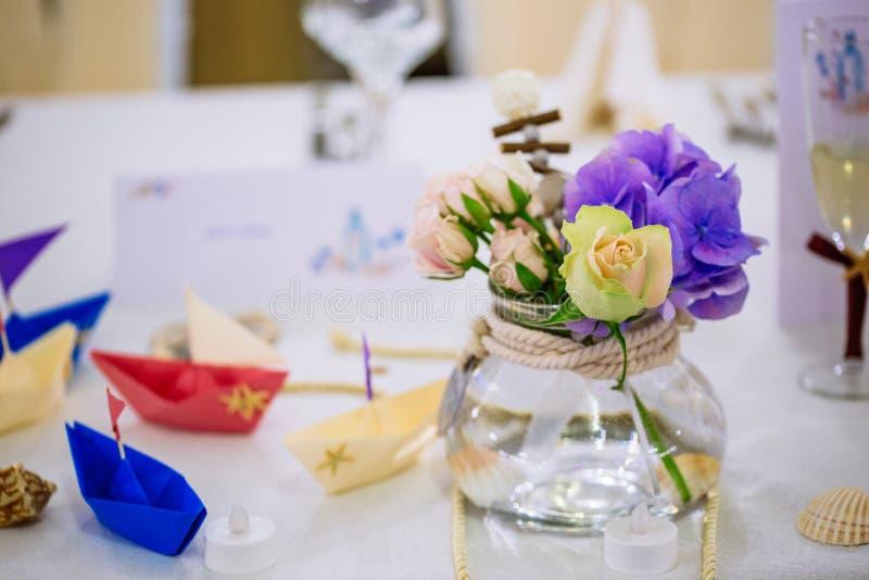 与花花束和origami小船的婚姻的船舶桌安排 免版税库存照片