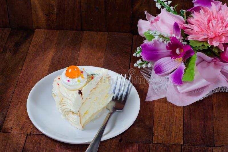 与花花束的奶油色蛋糕在木桌上的 库存图片
