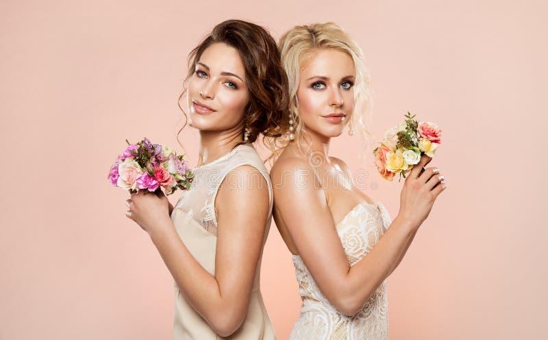 与花花束秀丽画象,美女演播室的两个时装模特儿射击与在头发的罗斯花 免版税库存照片
