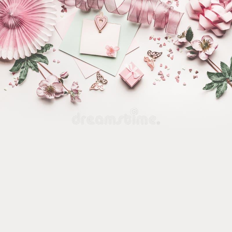 与花装饰、丝带、心脏、弓和卡片嘲笑的美丽的粉红彩笔工作区在白色书桌背景,顶视图 库存图片