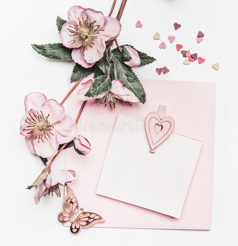 与花装饰、丝带、心脏和卡片嘲笑的可爱的粉红彩笔布局在白色书桌背景,顶视图,平的位置 我们 免版税库存图片