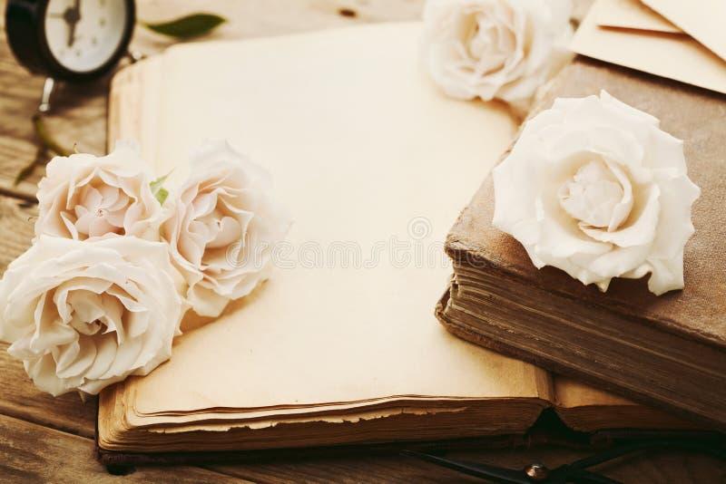与苍白玫瑰色花的减速火箭的静物画和打开古老书 在老木桌上的怀乡构成 图库摄影