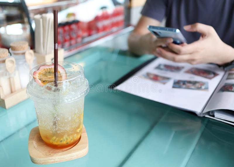 与苏打的西番莲果汁在一个人的桌和背景上使用流动智能手机的在餐馆 库存图片