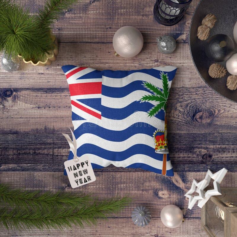 与英属印度洋领地旗子的新年快乐标记在枕头 在木桌上的圣诞装饰概念与可爱 免版税库存图片