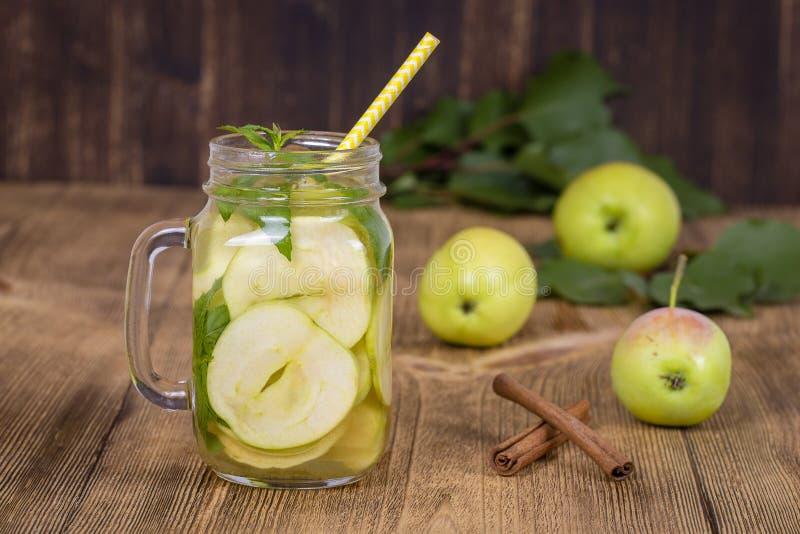 与苹果切片和薄荷叶的饮食戒毒所饮料在净水和在一张木桌上的一个新鲜的苹果 免版税库存照片