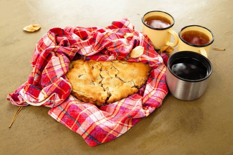 与苹果饼的秋天静物画在一块红色方格的毛巾和三杯茶在桌上的 库存图片