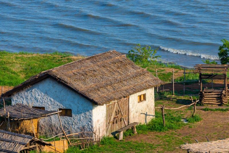 与茅屋顶的老传统白色小农场村庄,有海湾的海的 被隔绝的秀丽,保护,修造的wi的概念 免版税库存照片