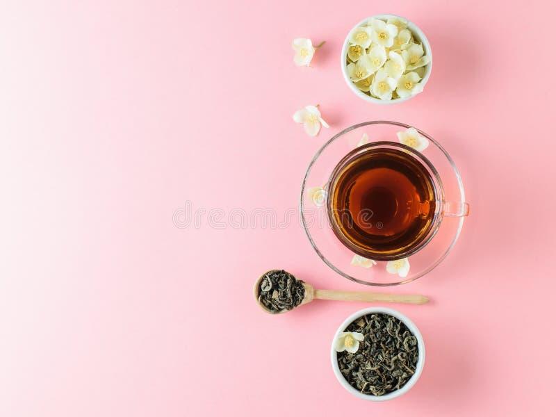 与茉莉花和一个碗的清凉茶在一张桃红色桌上的花 早晨早餐舱内甲板位置的构成 免版税库存图片