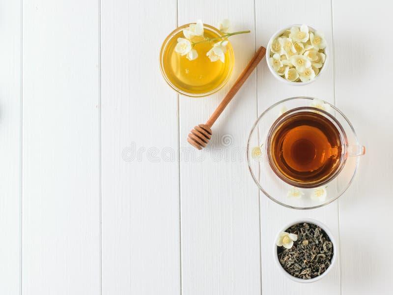 与茉莉花花和蜂蜜的新作茶在一张白色木桌上 平的位置 春天茶构成 免版税库存照片