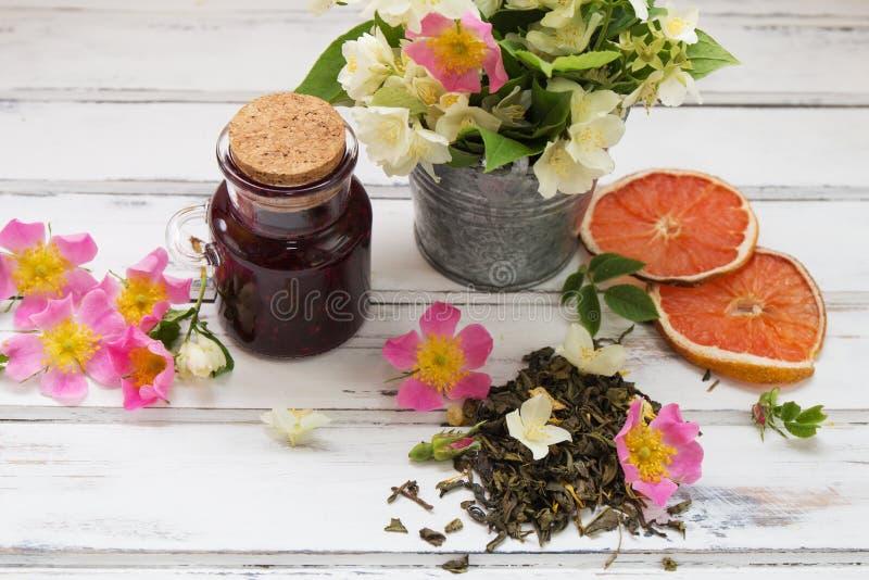 与茉莉花花的茉莉花干绿色茶叶,与狂放的玫瑰和山莓果酱花  库存照片