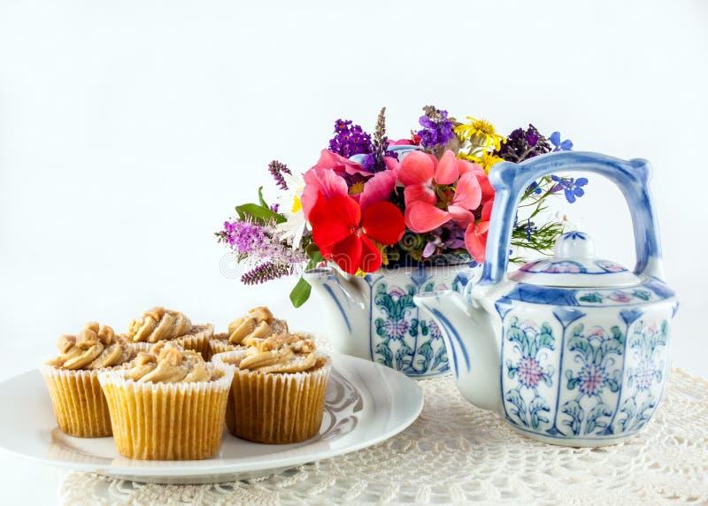 与茶壶花的杯形蛋糕 图库摄影