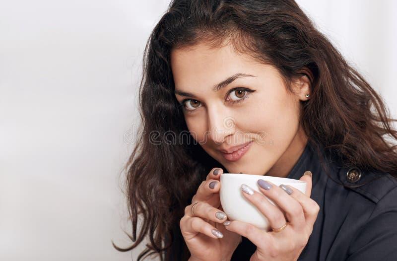 与茶的少妇画象或咖啡,与黑卷发的美丽的面孔特写镜头 免版税库存照片