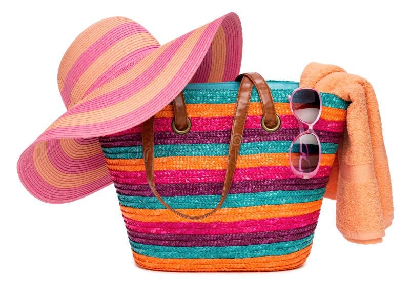 与草帽毛巾和太阳镜的五颜六色的镶边海滩袋子 库存照片
