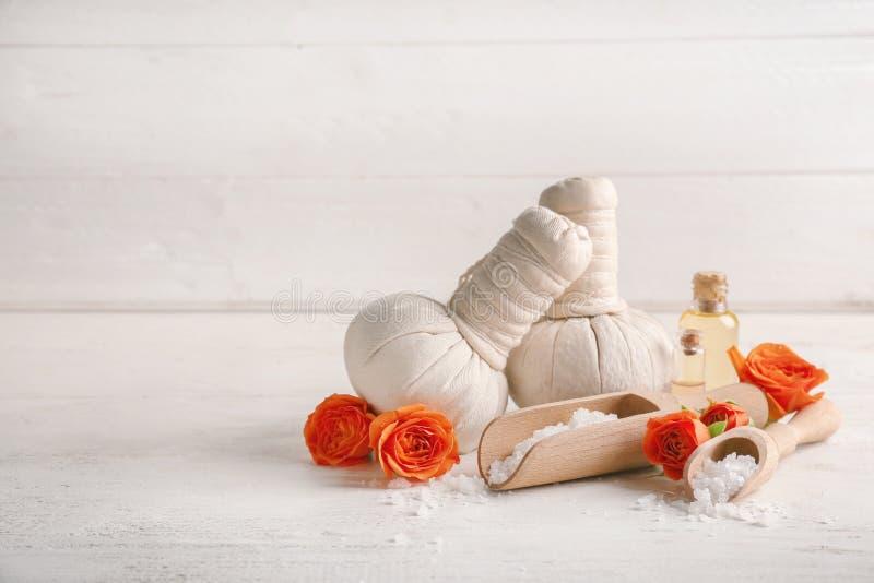 与草本袋子、海盐和瓶的美好的温泉构成在白色桌上的精油 库存图片