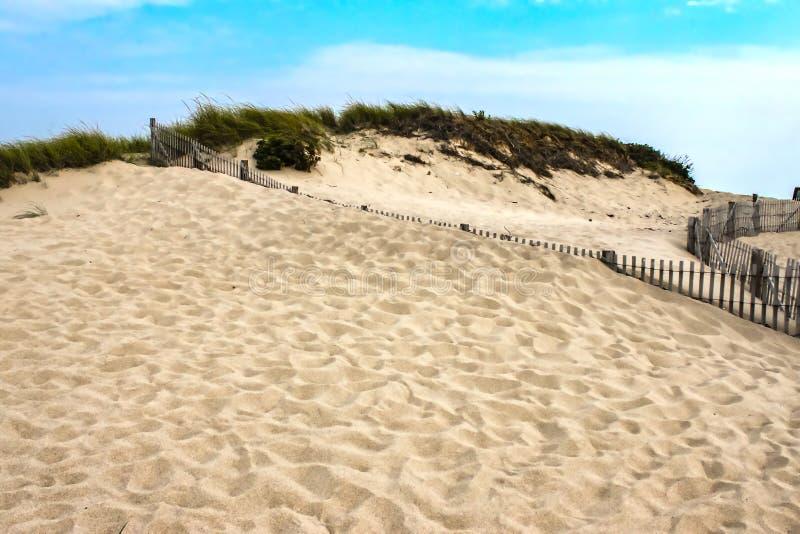 与草的沙丘在上面和在前景的许多脚步与几乎保留有沙子的篱芭对在一俏丽的天空蔚蓝下的上面 库存图片