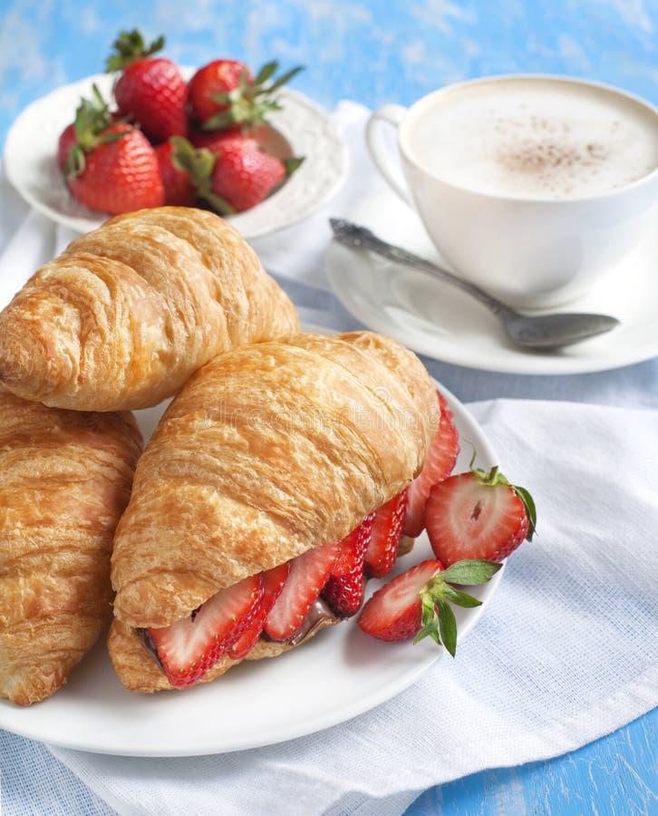 与草莓和巧克力坚果奶油的新鲜的新月形面包 免版税库存图片