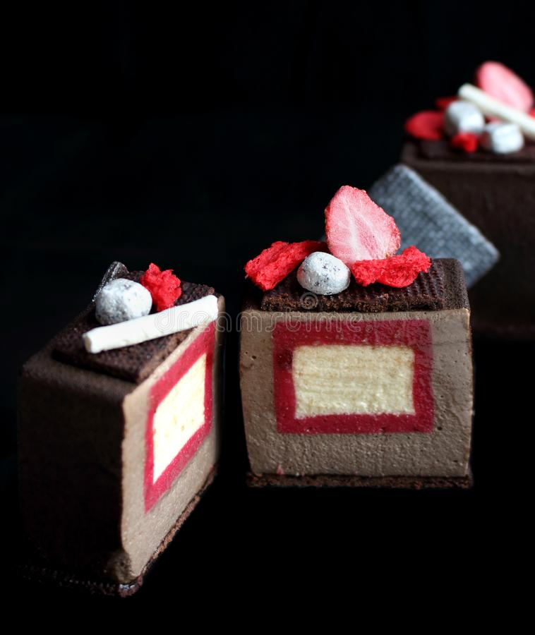 与草莓和香草插入的切的黑暗的巧克力织地不很细立方体点心,银色曲奇饼装饰和红色 库存图片