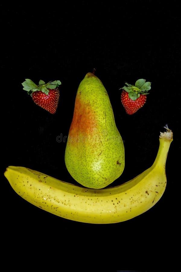 与草莓眼睛的微笑的果子面孔 免版税库存图片