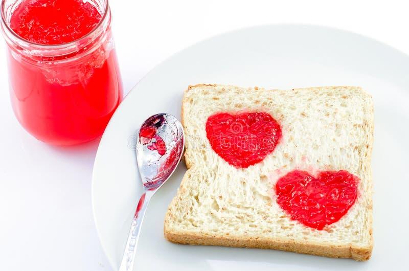 与草莓酱心脏形状的全麦面包在白色pl的 图库摄影