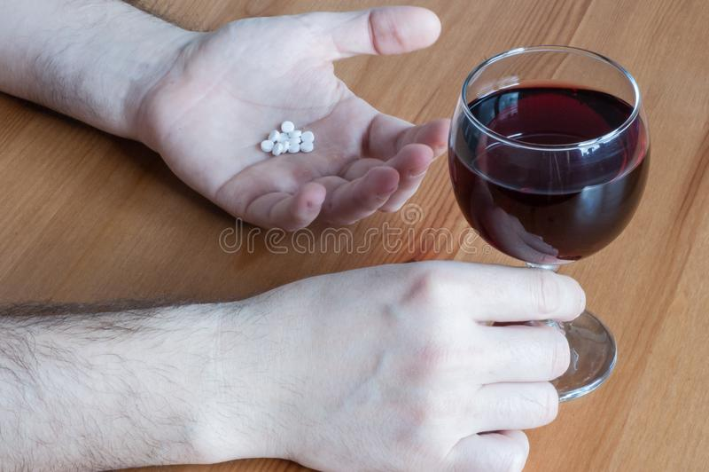 与药片抗生素红酒酒杯白色手桌特写镜头概念组合的混合酒精 库存图片